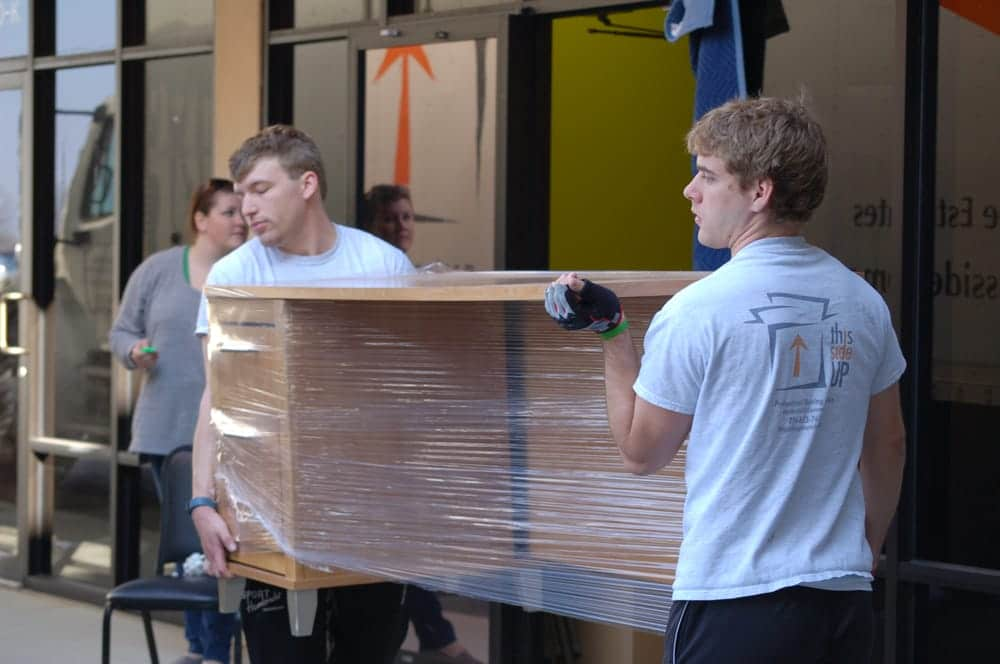 two movers carrying a desk onto a moving truck